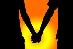 O dia de Valentim feliz, par da silhueta guarda a mão no céu crepuscular do por do sol Imagens de Stock