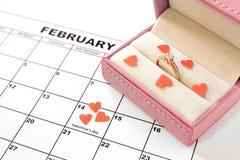 O dia de Valentim, o 14 de fevereiro no calendário com corações e a caixa de presente vermelhos fotografia de stock