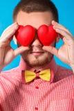 O dia de Valentim. Homem considerável com dois corações em suas mãos fotografia de stock
