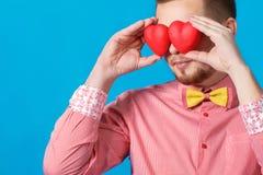 O dia de Valentim. Homem considerável que guarda dois corações imagem de stock