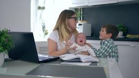 O dia difícil, mamã do negócio com o infante de grito nos braços grita no filho o mais idoso e então da tomada cabeça à disposiçã video estoque