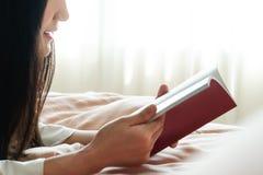 O dia do livro do mundo, mulher coloca na cama que lê o livro vazio foto de stock