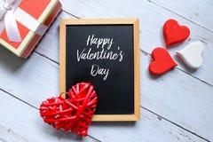 O dia feliz do ` s do Valentim escrito em um quadro-negro com coração de madeira vermelho e branco handcraft e uma caixa Fotografia de Stock Royalty Free