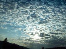 O dia nebuloso com Sun irradia nas nuvens Imagens de Stock