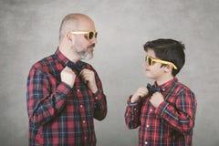 O dia, o pai e o filho de pai com laço e óculos de sol imagens de stock royalty free