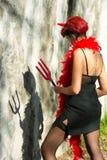 O diabo da mulher olha sua sombra Fotos de Stock Royalty Free