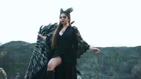 O diabo escuro inspeciona sua possess?o, menina com as asas pretas maci?as e chifres em sua cabe?a em pedras pr?ximo, senhora com filme
