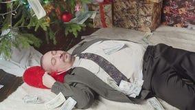 O dinheiro cai em um homem que dorme perto de uma árvore de Natal vídeos de arquivo