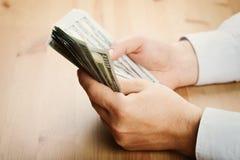O dinheiro da contagem do homem desconta dentro sua mão A economia, economia, salário e doa o conceito imagens de stock royalty free