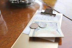 O dinheiro de Japão (iene) e de conta para refeições na tabela Fotos de Stock Royalty Free