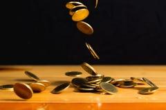 O dinheiro de queda das moedas de ouro na tabela de madeira com parede preta, copia s Fotos de Stock
