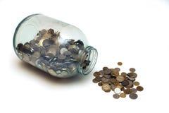 O dinheiro derramou de um frasco de vidro em um fundo branco imagens de stock royalty free