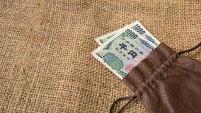 O dinheiro dos ienes e os ienes inventam com o passaporte no fundo do saco Fotografia de Stock