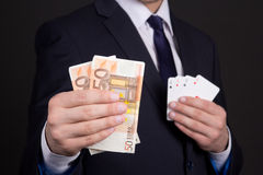O dinheiro e quatro cartões dos áss equipam dentro as mãos Imagens de Stock Royalty Free