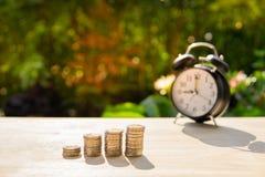 O dinheiro inventa a barra e o despertador e a pilha do borrão no fundo de madeira da tabela e do por do sol nas economias da mos foto de stock