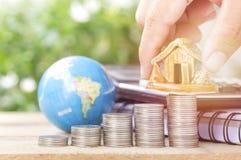 O dinheiro posto mão na pilha das moedas, o globo e a casa, conceito no crescimento, venda, compra, economias e investem no negóc foto de stock