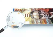o dinheiro rendido 3D de Arábia do israelita com lente de aumento investiga a moeda no fundo branco Fotografia de Stock Royalty Free