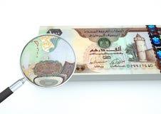 o dinheiro rendido 3D de Emiratos Árabes Unidos com lente de aumento investiga a moeda no fundo branco Fotos de Stock Royalty Free