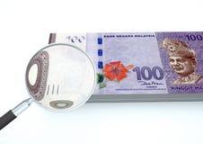 o dinheiro rendido 3D de Malásia com a lente de aumento investiga a moeda isolada no fundo branco ilustração royalty free