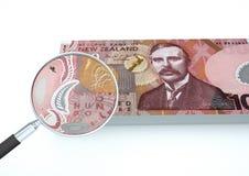 o dinheiro rendido 3D de Nova Zelândia com a lente de aumento investiga a moeda isolada no fundo branco ilustração do vetor