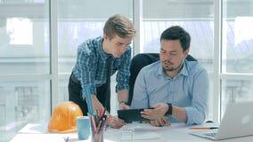 O diretor discute o projeto com o empregado, dá o conselho, usando a tabuleta digital no escritório moderno novo filme