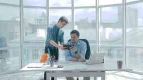 O diretor discute o projeto com o empregado, dá o conselho, usando a tabuleta digital no escritório moderno novo vídeos de arquivo