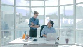 O diretor discute o projeto com o empregado, dá o conselho, usando a tabuleta digital no escritório moderno novo video estoque