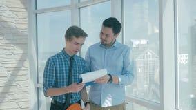 O diretor discute o projeto com o empregado no escritório moderno novo vídeos de arquivo
