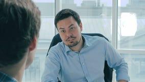 O diretor discute o projeto com o empregado no escritório moderno novo video estoque
