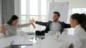 O diretor e os empregados felizes na ruptura, café-ruptura no escritório, executivos bebem o café na tabela, equipe criativa filme
