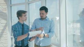 O diretor feliz discute o projeto com o empregado no escritório moderno novo video estoque