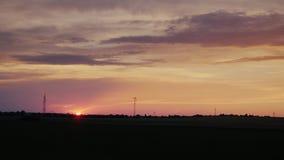 O disco do sol de ajuste sobre o campo no campo Vista da janela de um carro movente filme