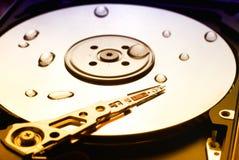 O disco rígido do computador com cabeça e água de leitura deixa cair nele fotografia de stock
