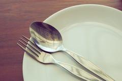 O Dishware ajustou-se na tabela de madeira com placa, colher e forquilha fotos de stock