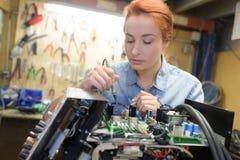 O dispositivo da eletrônica do reparo do técnico da jovem mulher tonificou a imagem imagem de stock royalty free