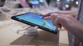 O dispositivo de teste, cliente usa o tablet pc moderno com o tela táctil na loja da eletrônica vídeos de arquivo