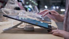 O dispositivo de teste do comprador, menina usa o tablet pc moderno com o tela táctil na compra na loja da eletrônica filme