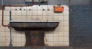 O dissipador velho na frente da parede telhada fotografia de stock royalty free