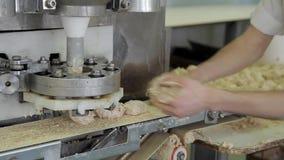 O distribuidor automático forma partes da massa na padaria dentro filme