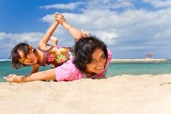 O divertimento asiático da matriz e da criança joga na praia Imagem de Stock