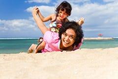 O divertimento asiático da matriz e da criança joga na praia Foto de Stock Royalty Free