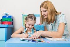 O divertimento da menina e da mãe em um caderno tira Fotografia de Stock