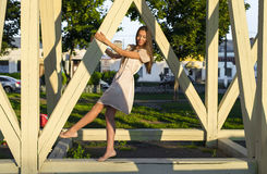 O divertimento de relaxamento do vestido moreno feliz da mulher que inclina-se no parque de madeira das pilhas aprecia suas féria Imagens de Stock Royalty Free