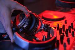 O DJ entrega fones de ouvido da posse perto do misturador na luz vermelha closeup Fotografia de Stock Royalty Free