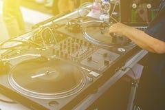 O DJ entrega vibrações da música do jogo em um partido da praia do verão que usa uma plataforma giratória da instalação da plataf fotografia de stock