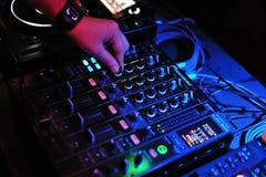 O DJ mistura e jogando com o misturador pioneiro e consola Foto de Stock