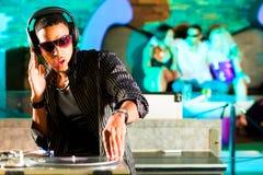 O DJ no disco bate, aglomera o fundo Fotografia de Stock