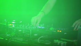 O DJ profissional trabalha o close-up no soundbar em um partido do clube noturno lighting filme
