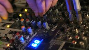 O DJ trabalha no console do misturador Mão que ajusta o misturador audio vídeos de arquivo
