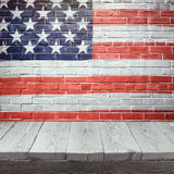 4o do fundo de julho com a tabela de madeira sobre a bandeira dos EUA pintada na parede de tijolo Imagem de Stock Royalty Free